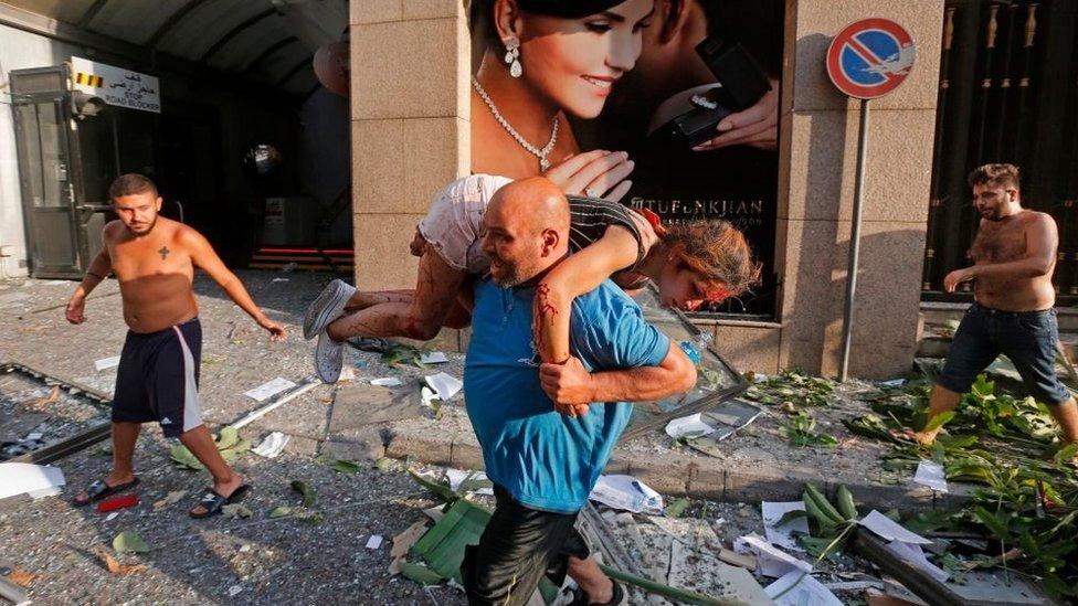 <p>Getty Images</p><p>Beyrut'ta bir kişi yaralanmış bir kızı taşıyor</p>